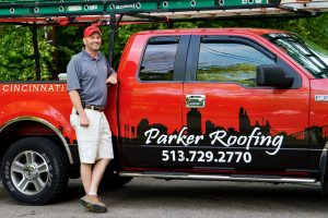 A man stands in front of a red truck with the Parker Roofing logo on it.