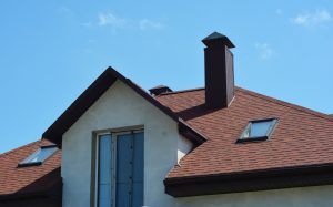 A close-up of an asphalt shingled roofing construction with attic skylights, a chimney, soffit, fascia board and roof gutters installed.